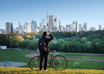 A woman standing beside a bike looking at the Toronto skyline.