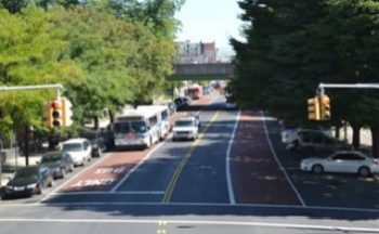 A bus driving towards an intersection on an offset bus lane