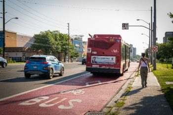 A bus travelling on the RapidTO: Eglinton East Bus Lanes identifed by the red pavement paint and markings.