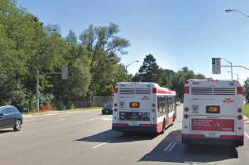 Two buses travelling side-by-side, as one bus is it is travelling on the HOV lanes on Don Mills Road.
