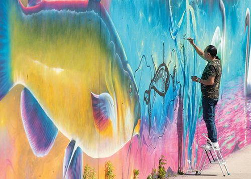 Artist painting on a street wall