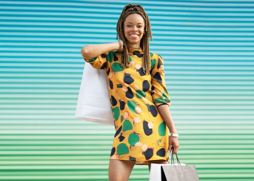 Person in yellow dress holding shopping bags and smiling at the camera