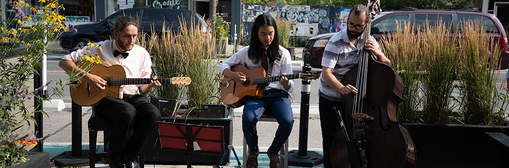 Local band of three people performing live music on a cafe patio.