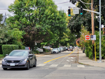 Car driving south on Woodfield Road at Dundas Street East, with a contra-flow bicycle lane in the opposite direction.
