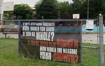 Banner with text of a poem hung against a chain link fence with outdoor basketball court in the background