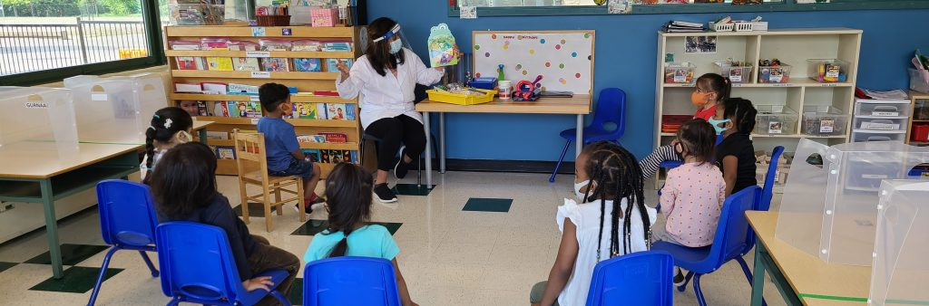 An Early Childhood Educator reads to a group of children
