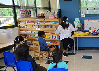 An Early Childhood Educator reads to a group of children.